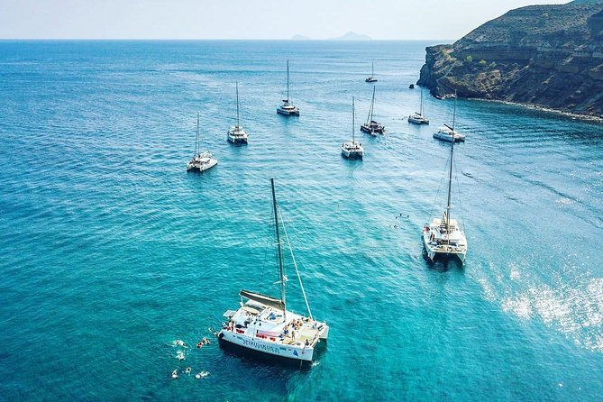 Sail around Santorini on aCatamaran during this 5-hour Cruise, departing from Vlychada Marine. Sail past the island's highlights, such as the Venetian Lighthouse, the Indian Rocks, the Red & White Beaches and the Village of Akrotiri. Stop at the White Beach for a swimming and snorkeling session and enjoy scenic views of the Aegean Sea as well as the neighbouring Greek Islands on your way back. BuffetLunch or Dinner& Open Bar on board the boat are included. Choose between Daytime or Sunset Cruise upon Booking.