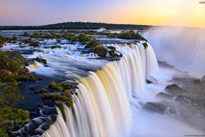 Visit the Iguazu Falls, the largest waterfalls system in the world, in this unique full day tour. You will tour the Argentinian Side of the Falls which conteins an 80% of the total jumps of the falls.<br><br>This amazing place was designatedUNESCOWorld Heritage Site and one of the New 7th Wonders of Nature.<br><br>You will be able to to choose to travel among a group tour (up to 40 passengers) or a small-group tour (up to 20 passengers), assuring that you choose your own experience.<br><br>Inside the park, you will be able to perform different activities, if you want to get the chance to get to know the forest and the falls closer than anyone, do not hesitate to choose the boat ride options we have for you!