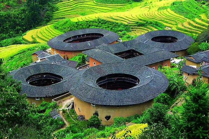 """Tianluokeng Earthen Building Cluster — The Classic Cluster<br><br>Among the more intriguing pieces of history in Fujian are the tulou -- large, round, rammed-earth buildings dating back centuries. Tianluokeng tulou cluster, have been inscribed in 2008 by UNESCO as World Heritage Site, as exceptional examples of a building tradition and function exemplifying a particular type of communal living and defensive organization, and in terms of their harmonious relationship with their environment. Tianluokeng Earthen Building Cluster is a neat Olympic-rings-shaped group of five earthen buildings: one square building and four round buildings around it. Many travelers call it """"four dishes and one soup""""."""