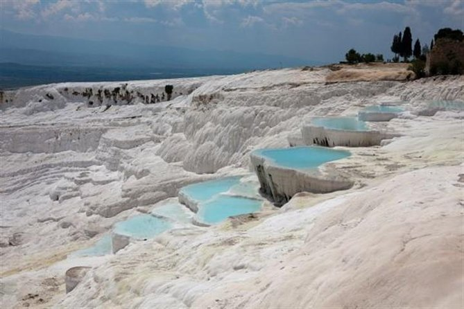 Witness one of Turkey's most phenomenal natural wonders – the UNESCO World Heritage Site of Pamukkale – on this 10-hour guided day trip from Kusadasi. Visit the ancient spa city of Hierapolis, stroll in the warm waters of the brilliant white travertines, swim in natural hot springs full of Roman ruins, and enjoy a Turkish restaurant lunch.