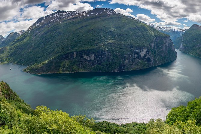 "A memorable half day tour in Geiranger and its surroundings. During this three and an half hour excursion you will depart from Geiranger by bus. Experience the Eagle Road with its 11 hairpin curves and enjoy the breathtakingly beautiful view over the majestic Geirangerfjord and several waterfalls, including the ""Seven Sisters"". Driving along the Lake of Eidsdal the road continues to the idyllic Herdal Summer Farm, where you will find goats, cows and fjord horses. The owners will gladly invite you to taste their delicious homemade goat cheese."