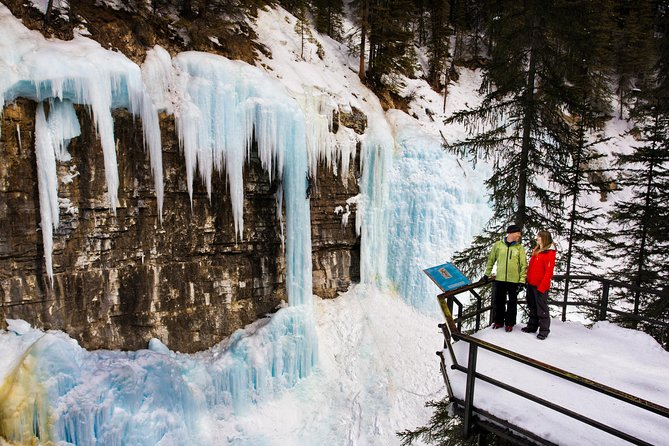 """Trek through Johnston Canyon to a world of frozen waterfalls and pillars of blue ice. Learn about the formation of the canyon, discover fossil corals in the rocks, and photograph the incredible pillars of iceas you walk through the canyon bottom and over suspended catwalks.  Yourprofessional guideleads you past waterfalls frozen in mid-stream,and through a short tunnel for a close up view of the Lower Falls! The grand finale is the incredible """"Cathedral of Ice"""" at the Upper Falls. Includes hot cocoa and fresh baked cookies! Activity Rating: Moderate"""