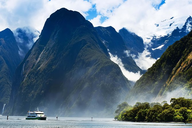 Admire the spectacular sights of Milford Sound on a scenic cruise aboard a modern, spacious and comfortable catamaran. <br><br>Look out for dolphins, seals and penguins against a backdrop of cascading waterfalls and a luxuriant rainforest as you marvel at one of the world's most incredible natural wonders<br><br>Visit the open top deck for unlimited 360 degree views and photo opportunities, or choose a beverage from the on board bar during Happy Half Hour.<br><br>Take the opportunity to meet the skipper in the open wheelhouse, or if you're feeling adventurous, join the friendly crew for a free glacial shower as the boat noses under Stirling Falls. <br><br>Choose to self drive and meet at the pier or take an optional bustour from Queenstown or Te Anau through Fiordland National Park to Milford Sound.