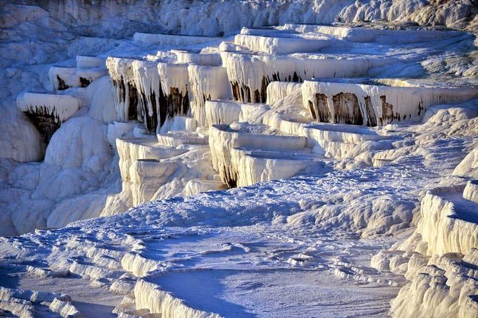 Pamukkale is a fairyland of dazzling white, petrified castles. Thermal spring waters laden with calcareous salts running off the plateau's edge have created this fantastic formation of stalactites, cataracts and basins. The hot springs have been used since Roman times for their therapeutic powers. Pamukkale is one of the most interesting places in the world, justly famous not only for the entrancing beauty of its unique geological formations but also for its historical remains