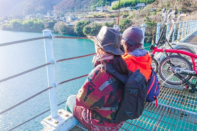 """On this tour, you cycle around the Ikeda Reservoir formed in the middle of the Yoshino River.<br><br>The town of Ikeda, known as """"the navel of Shikoku"""" has always prospered as a center of trade. After cycling through the retro shopping street, you come to a row of old merchant houses with ornamental 'udatsu' firewalls.<br><br>A slight rise brings you to the Yoshino River, which has the largest flow of Japan's rivers. The deep reservoir and the man-made structures create a beautiful contrast.<br><br>This tour takes you through a historic town, along the magnificent Yoshino River, with a thrilling wire suspension bridge and a pretty submersible bridge. The route takes you along the Median Tectonic Line, one of the world's biggest faults. If the surface of the water is calm, the reservoir becomes a huge mirror."""