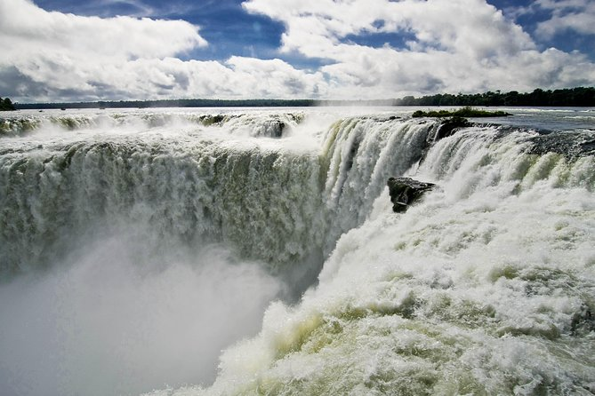 Explore Iguazu's impressive collection of waterfalls and feel the mist from the stunning 'Devil's Throat' on this overnight tour from Puerto Iguazu. Skip the hassle of dealing with logistics as we take care of your round-trip transportation.<br><br>Surrounded by tropical jungle and home to incredible biodiversity, discover 3 of the main walking trails and Iguazu Falls. Have an exciting ride on an eco-train that will lead you to the amazing 'Devil's Throat'. Admire its mesmerizing beauty and feel its power, one of the few experiences that will take you out of this world! <br><br>This tour allows you to make the most of your time Iguazu Falls, a true natural wonder of the world.