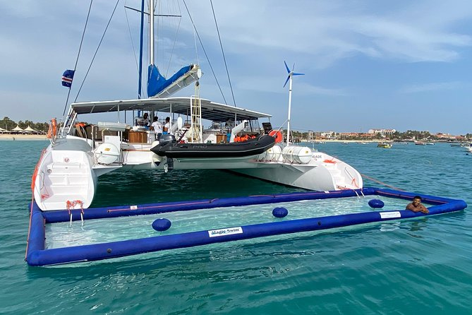 Our catamaran has a capacity of 90 people, but for the comfort of everybody a maximum of 60 people is allowed per tour. <br>It is very spacious and comfortable with open sitting areas with sofas, some lounge beds on the deck, nets with bean bags and private inflatable pool that can be set up when the boat is stopped halfway through the trip. We offer free Wi-Fi on board and charging points for small devices are available. <br>Drinks, both alcoholic and non-alcoholic are included as well as a freshly prepared snack.