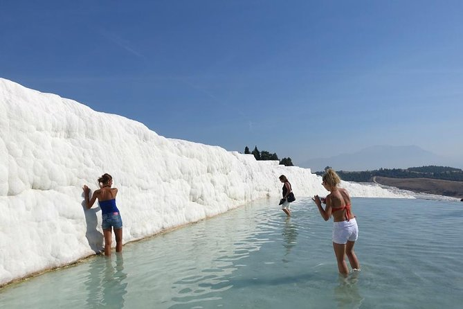 Immerse yourself in two of Turkey's most famous attractions on a 7-hour tour from Kusadasi or Pamukkale. <br>Skip the cramped public buses and relax in convenient all-inclusive transportation from your hotel. Enter the UNESCO listed site and enjoy a guided visit of the cotton colored Pamukkale travertines and ancient city of Hierapolis. Unwind in the natural baths with views of the city's ruins, then feast on lunch at a local restaurant. <br>-Eat lunch at a traditional Turkish restaurant <br>-Enjoy free time to soak in natural baths <br>-Travel comfortably by air-conditioned vehicle <br>-Explore a UNESCO World Heritage Site<br>
