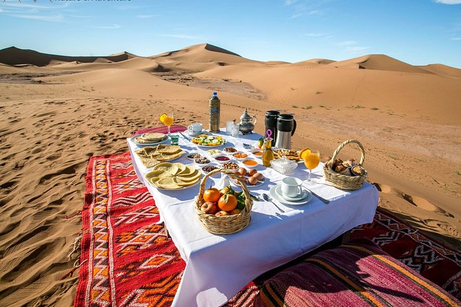 Ride a camel at Sunset through the majestic red sand dunes of Erg Lihoudi (2h per way)<br>Spend an unforgettable night under the shining stars at the beat of the desert drums in a luxury desert camp (double tent with private shower/toilet)<br>Enjoy a typical dinner and and evening under the stars<br>Try sandboarding from the top of the dunes<br>Marvel at the sunrise the next morning and enjoy your rich breakfast before riding back by camel to M'Hamid or Ouled Driss