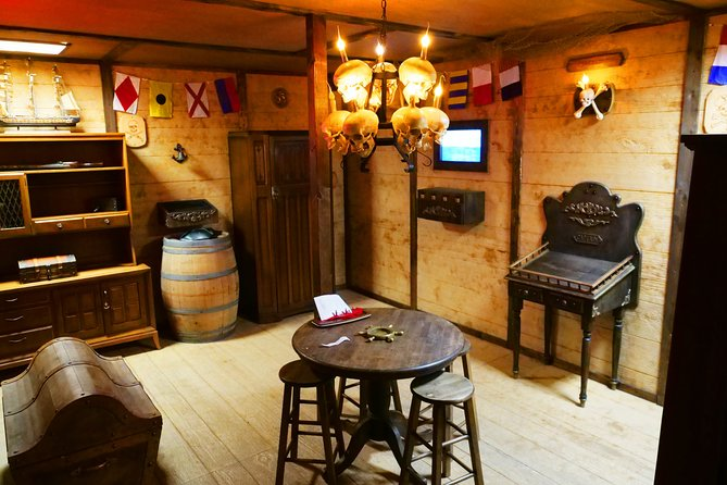 """""""The Pirate Chamber"""" takes place aboard The Queen Anne's Revenge in 1718... """"The Golden Age of Piracy.""""<br><br>Captain Edward Teach, best known to history as """"Blackbeard the Pirate"""", recently had his plans to sail for America disrupted by a group of sneak-thieves.<br><br>Though they only managed to make off with five pieces of a worthless decoy treasure map, Blackbeard realized his secrets aren't as safe as he thought...<br><br>Digging deep into his dastardly imagination, Blackbeard has deployed more devious devices to distract his detractors - All in the name of keeping the genuine treasure map containing the whereabouts of his REAL riches high and dry!<br><br>""""The Pirate Chamber - Heist on the High Seas: Chapter II"""" is the sequel to our critically-acclaimed original escape room experience! There are enough new clues, new puzzles, and new surprises to challenge newcomers and veterans alike!"""